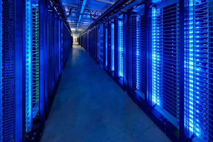 Blue-lit servers blink inside the Facebook data center in Prineville, Oregon, the hub of the company's global infrastructure. (Photo: Alan Brandt for the Open Compute Project)
